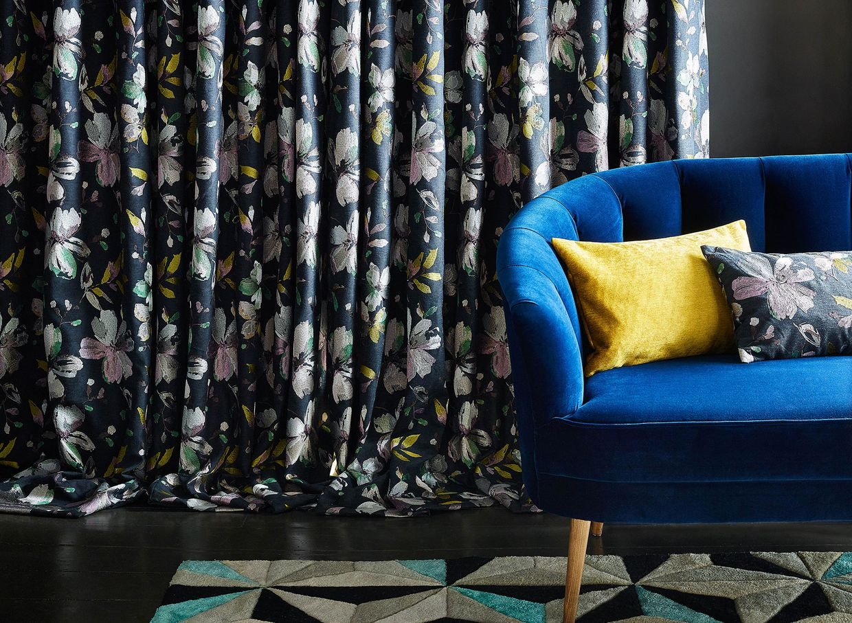Close up detail of blue sofa with dark floral curtain behind