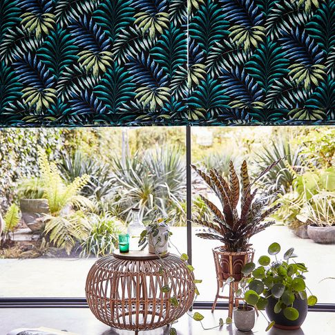 Green and yellow  printed roman blinds on patio door and cushions on leisure hanging chair