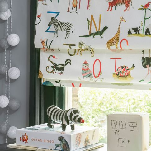Close up of ABC and animals printed Roman blinds in children's study room