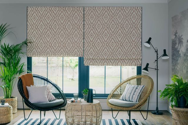 Cream patterned roman blinds in a white room that features large green plants. There are two wicker chairs with cushions in front of the window.