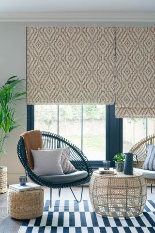Cream and brown diamond patterned Roman blinds in a blue garden room with plants