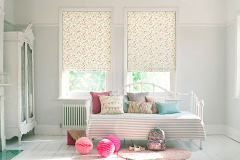 Kids bedroom with summery printed roman blinds and printed cushions on the bed