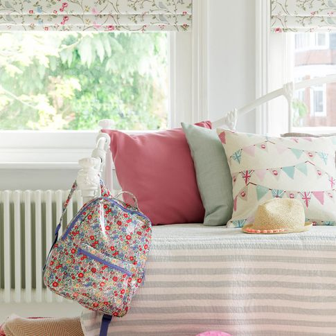 Close up of kids bedroom with summery printed roman blinds and printed cushions