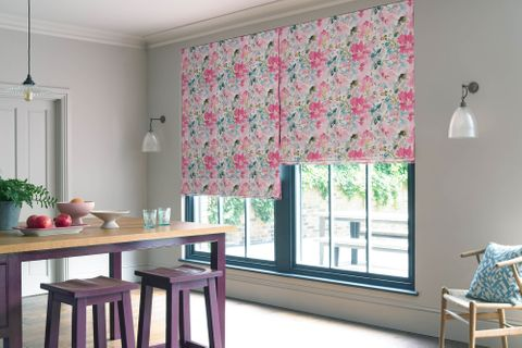 Pink, blue and purple floral roman blinds in a white dining room covering a blue window