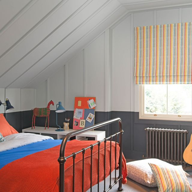 Striped roman blinds with mustard, orange and light blue colors in an attic bedroom