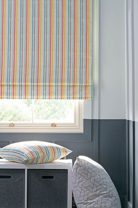 Striped roman blinds with mustard, orange and light blue colors and matching cushion in an attic bedroom