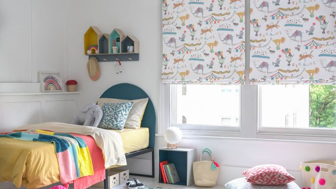 A children's bedroom featuring two windows that have a white blinds dotted with multi coloured circus animals