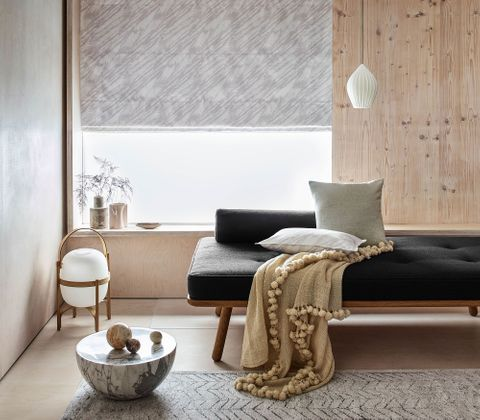 The room features a window partially covered with a soft grey Roman blind. In front of the window and to the left is a long black couch that has a beige throw draped across it. This room also has an exposed wooden wall and minimal accessories to the right of the chair