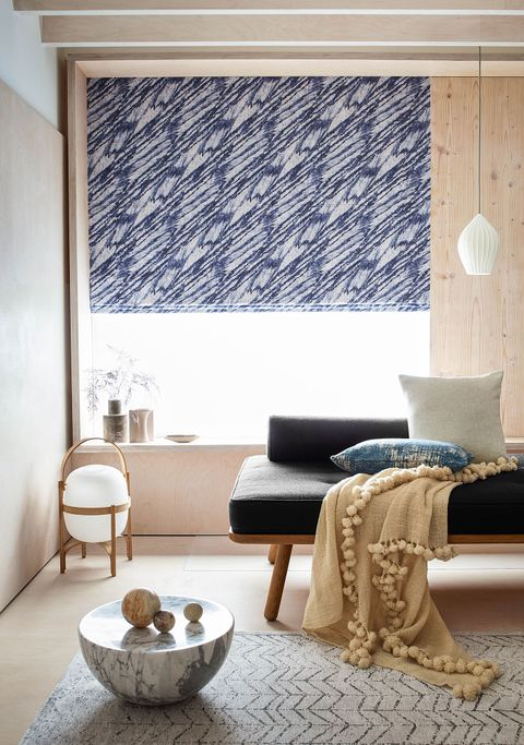 Blue patterned roman blinds hanging on a window in siting room, window is decorated with flower vases.
