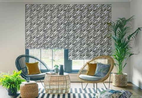 Black and white wave patterned roman blinds in a garden room decorated with wicker furniture and wicker chairs are placed with plain mustard and blue cushions.