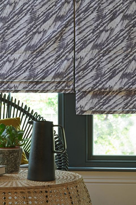 Close up of black and white wave patterned Roman blinds in garden room.