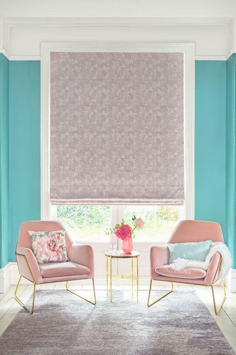 textured shimmering purple Roman blinds in living room. Light blue and printed cushions have been placed on two blush pink arm chairs with gold legs in the room