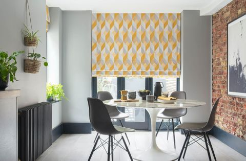 This grey and white room features a dining room table with four chairs. The long windows behind the table are covered with a Roman blind featuring a grey and yellow geometric diamond shaped design