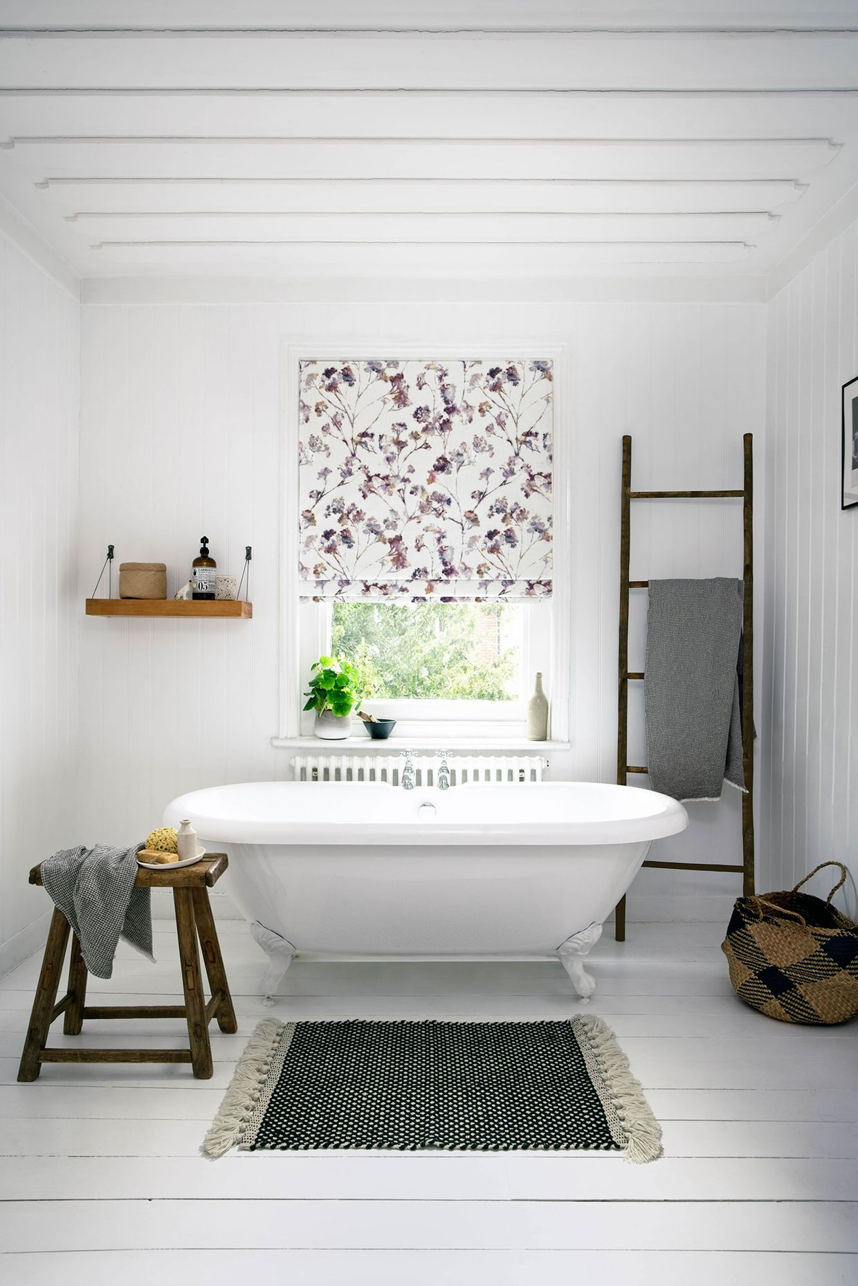 In this white bathroom  window behind the white bath is dressed with white roman blinds printed with pink and purple flowers.