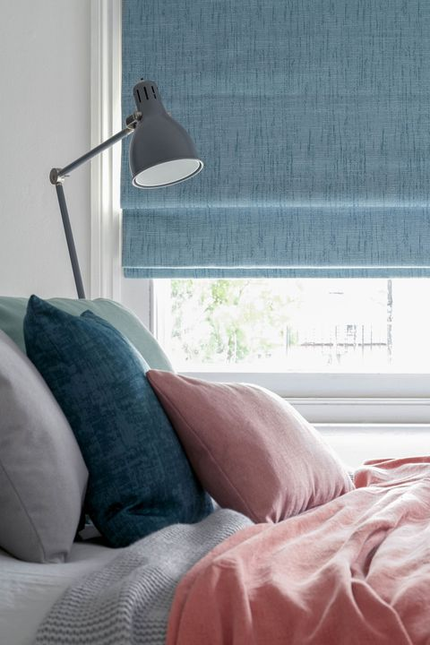 A window featuring a sky blue Roman blind is behind a bed piled with blue and pink cushions and a throw