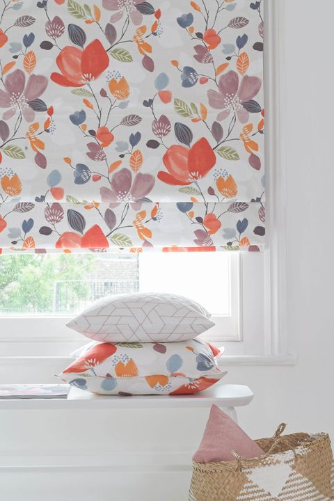Close up of warm toned floral printed roman blinds in a bed room window. Matching floral and patterned cushions have been placed on white table in the room.