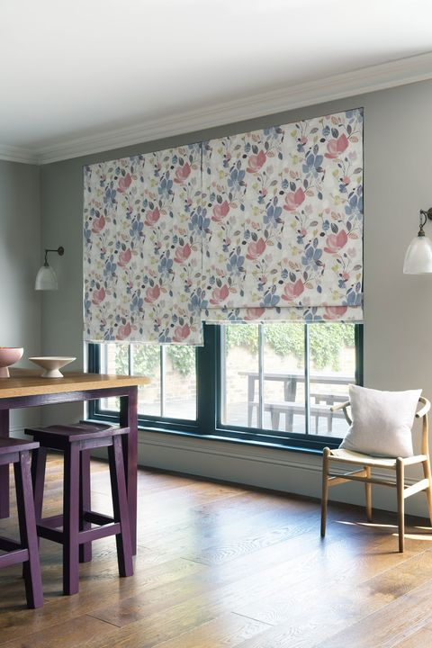 Layers of a Roman blind featuring a lavender, rose and yellow coloured floral pattern hang neatly in front of a window.