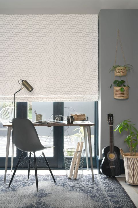 Layered roman blinds featuring Geometric grey shapes on a neutral white background hanging neatly on window of home office.