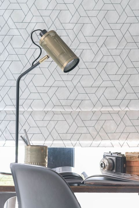 Close of roman blinds featuring geometric grey shapes on a neutral white background in a home office.