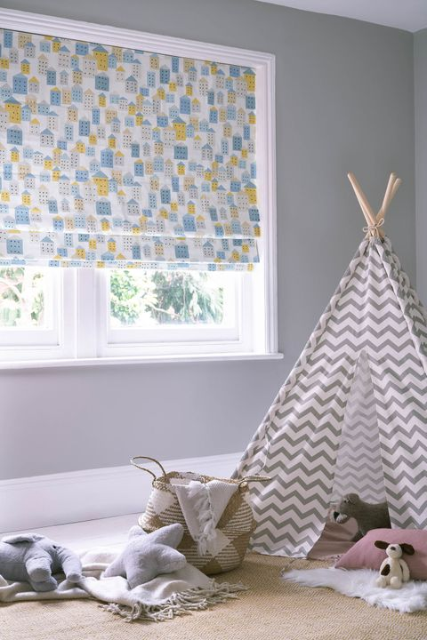 Children bedroom window dressed with roman blinds featuring Blue, grey and beige square design on a white background