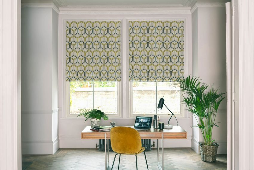 Window of home office behind office table dressed with roman blinds printed with geometric shapes in mustard and grey colors on white background