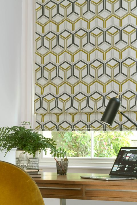 Close up of geometric printed shapes in mustard and grey colors Roman blinds in a home office