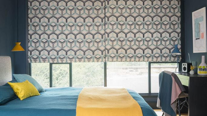 A geometric blue, white and black circular design featured on a Roman blind which is behind a blue bed with a yellow throw