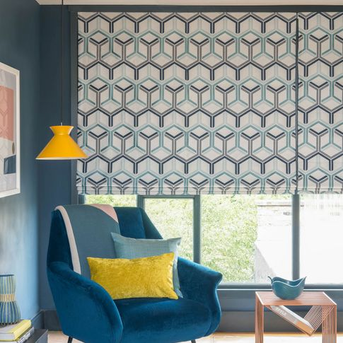 Close up of blue roman blinds featuring geometric shapes in teal and blue color on cream background. Light blue and mustard cushions have been placed on teal arm chair in the room.