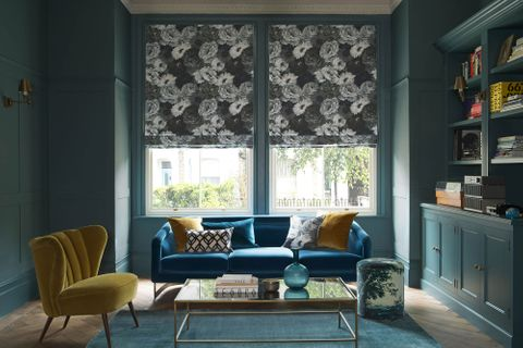 A blue couch rests in front of a window that is covered by a black floral Roman blind. The room is painted a deep forest green