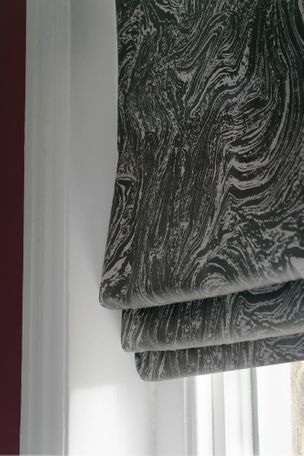 Close up of grey and silver marble effect black roman blinds in bathroom