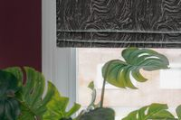A green monstera deliciosa plant rests below a white window on a deep red wall