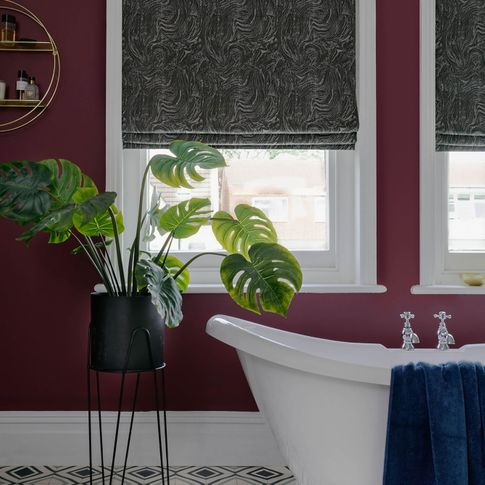 A deep wine bathroom with white bath and windows dressed with silver and grey marble effect roman blinds.