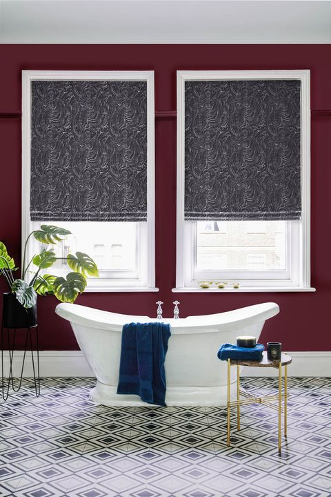A deep wine red bathroom featuring two white windows. The windows have a deep grey marble inspired Roman blind on them.