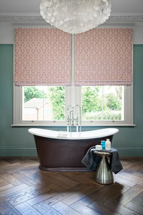 Two big windows in bath dressed with pink roman blinds featuring geometric shapes.