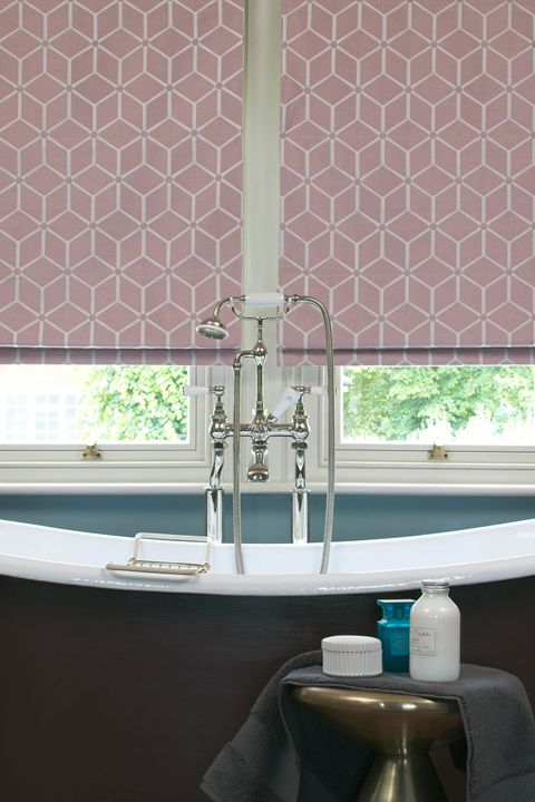 Close up of roman blinds in pink color featuring geometric shapes in a bathroom.
