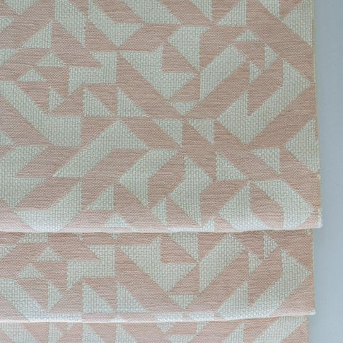 Close up of geometric peach and cream coloured Roman blinds