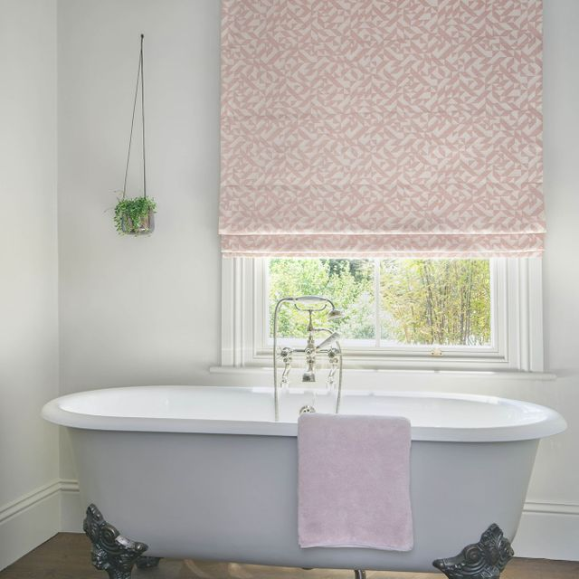Layered geometric peach and cream coloured Roman blinds featured neatly on a window in white bathroom