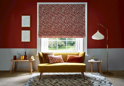A red and white room with a bright yellow couch that sits under the window. The window is covered with a Roman blind that features a red and white linear design