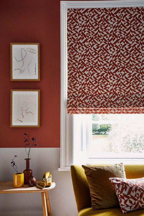 Corner view of a red and white room with a bright yellow couch that sits under the window. The window is covered with a Roman blind that features a red and white linear design