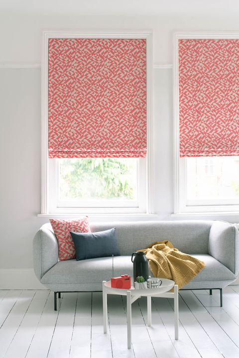 Windows of room white room are dressed with roman blinds featuring linear print in bright red and white color. Cushion matching to roman blinds have been placed on grey sofa.