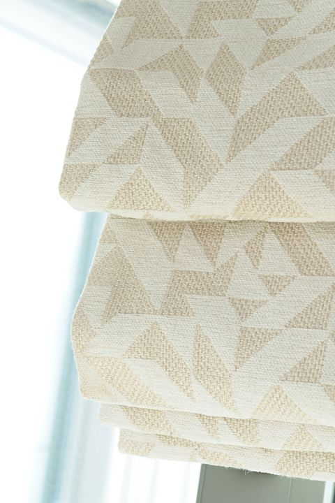 Close up of cream geometric printed Roman blinds