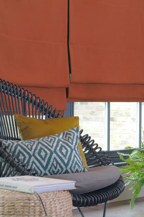 View of a window dressed with orange plain roman blinds. Blue patterned cushion and mustard plain cushion have been placed on a wicker chair resting in front of window.