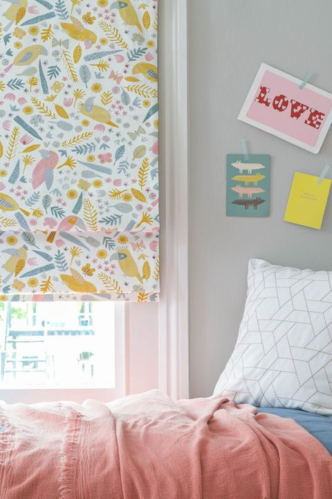 Corner view of kids bedroom window dressed with roman blinds featuring tucan print on white background