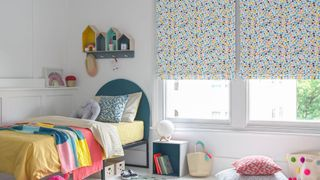 Children bedroom window dressed with roman blinds featuring multi-coloured dot pattern on a white background. Geometric printed cushions have been placed on  blue bed and rug in the room.