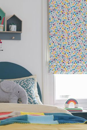 Corner view of a kids white bedroom window dressed with roman blinds featuring multi-coloured dot pattern on a white background