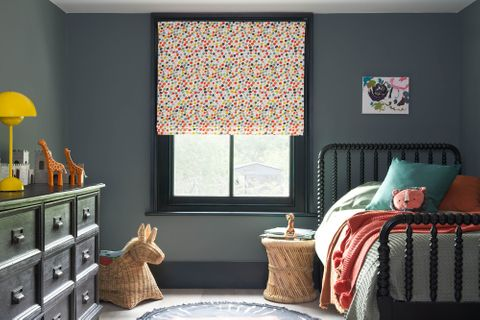 A grey children's bedroom with multi-coloured dotty Roman blinds