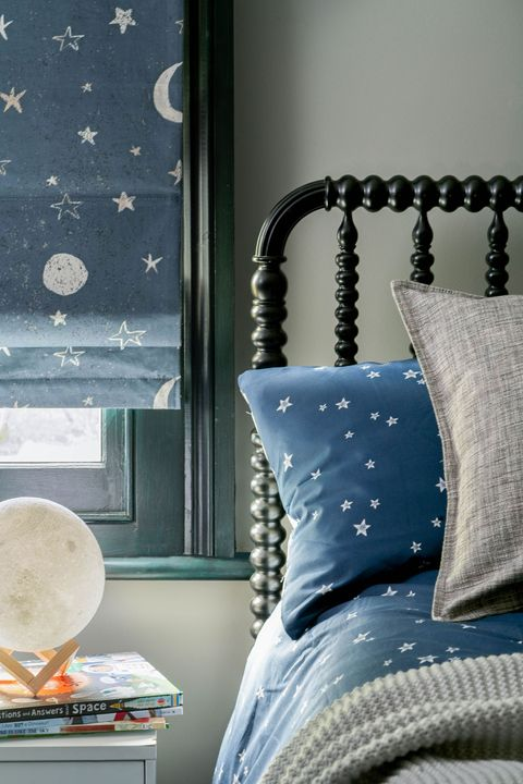 View of blue roman blinds printed with stars and moon hanging on a kids bedroom window. Bed is dressed with blue cushion printed with white stars.