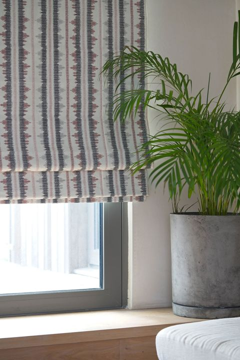 View of window dressed with a tribal-inspired Roman blind in red and brown accents on a white background