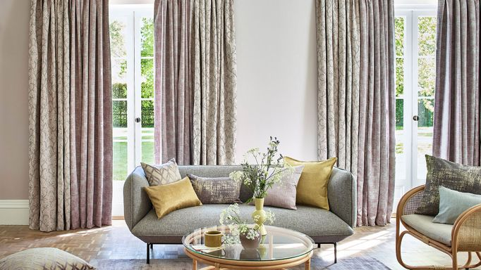 Neutral beige featuring delicate embroidery curtains and  textured shimmering purple curtains hanging on doors in living room