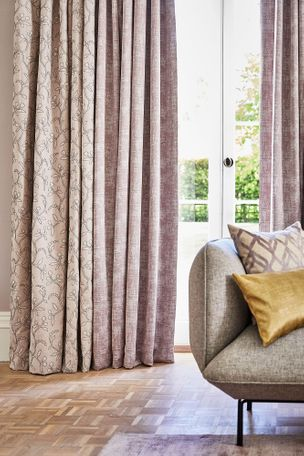 Neutral beige featuring delicate embroidery curtains and  textured shimmering purple curtains hanging on doors in  living room. A patterned cushion and a plain mustard cushion has been placed in corner of sofa